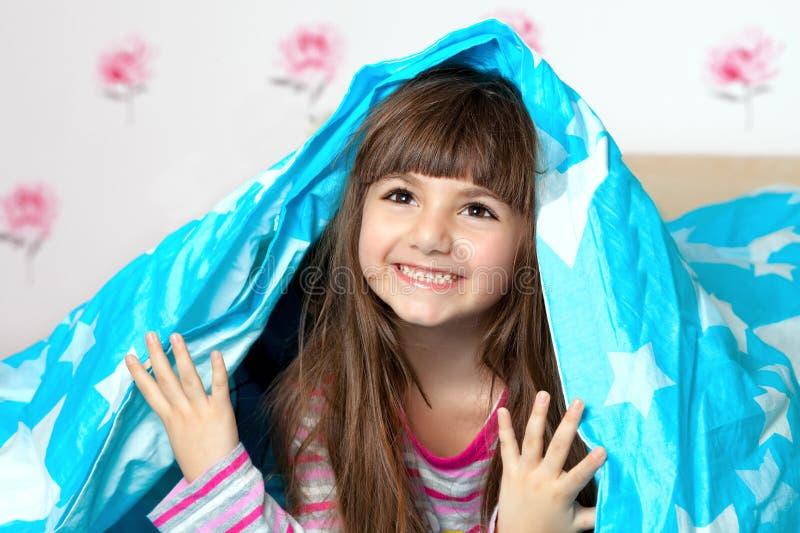 Menina sob o cobertor fotografia de stock