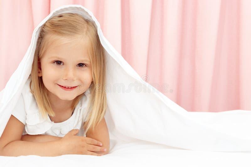 Menina sob o cobertor foto de stock