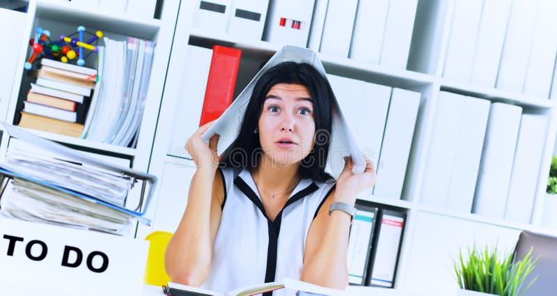 A menina sobrecarregado engraçada com um dobrador em sua cabeça que senta-se no local de trabalho desordenou com dobradores Reaçã foto de stock royalty free