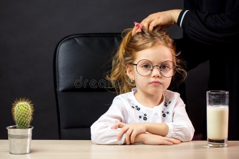 Menina sombrio nos espetáculos que recusa beber o leite, sobre o backgrounf preto fotografia de stock royalty free