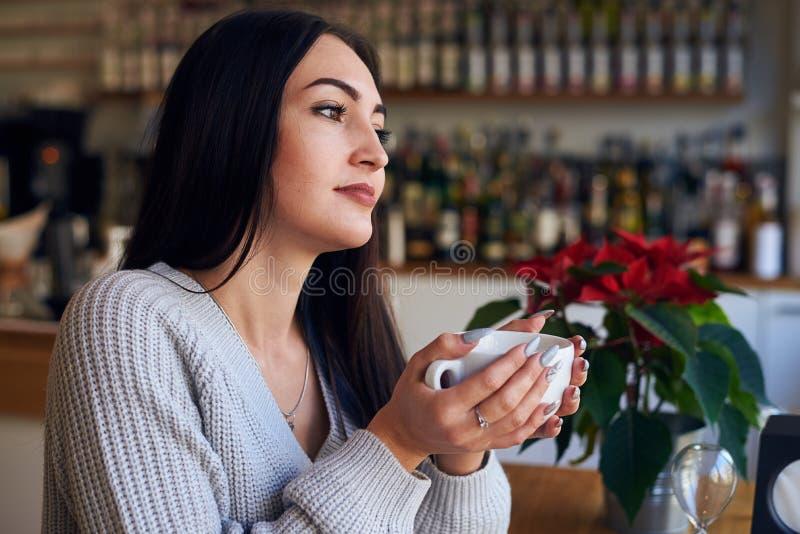Menina sonhadora que guarda a xícara de café um café imagens de stock