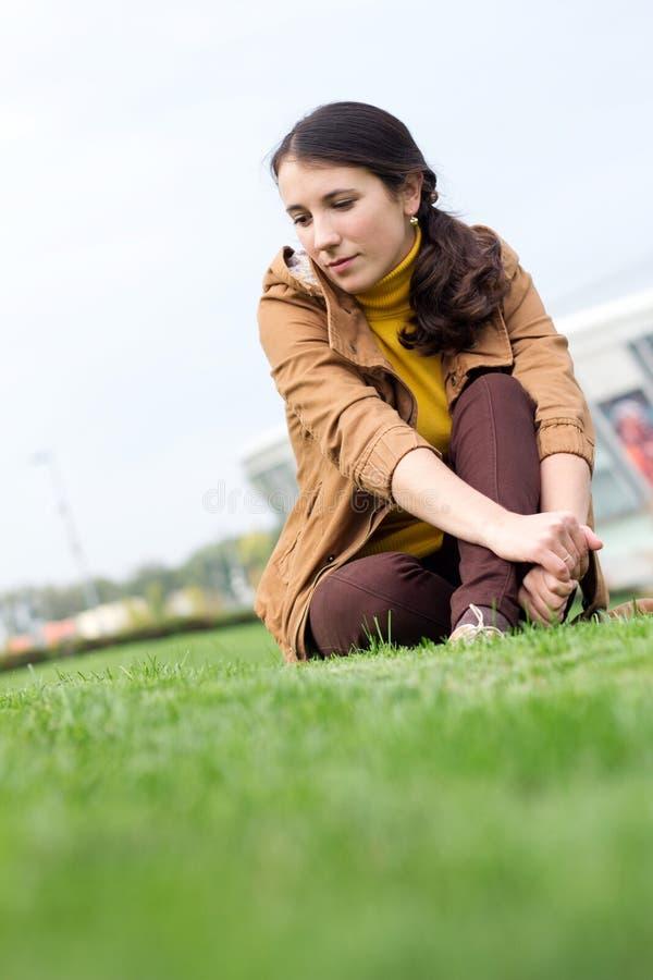 Menina sonhadora que senta-se em uma grama em um céu e em uma construção do fundo imagem de stock royalty free