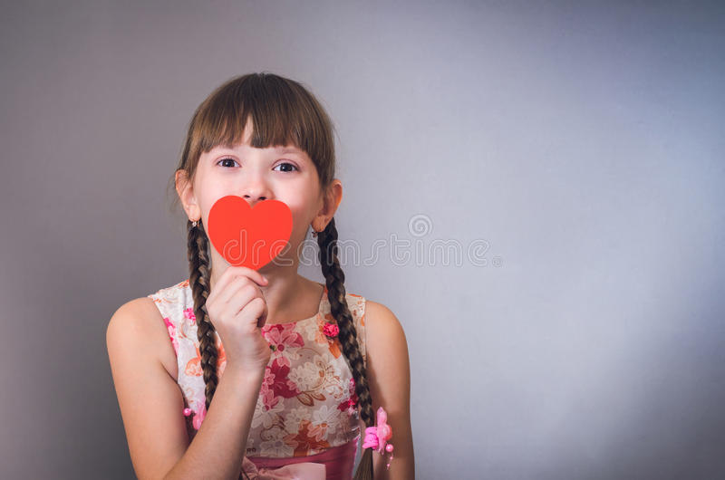 A menina sorri e fecha um coração da boca imagens de stock