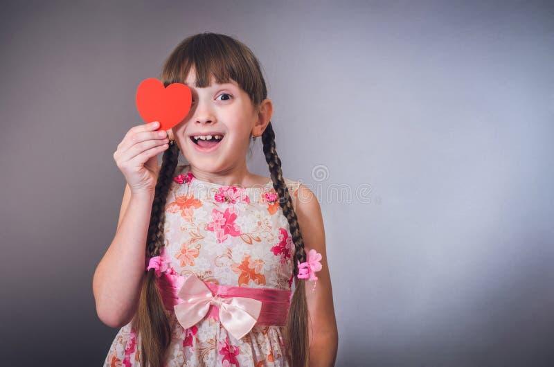 A menina sorri e fecha um coração do olho imagem de stock