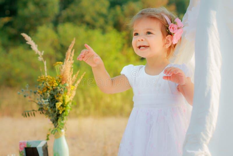 A menina sorri e mostra o dedo para cima Uma menina em uma barraca branca da tenda ou do jogo, casa do jogo do ` s das crianças fotografia de stock royalty free