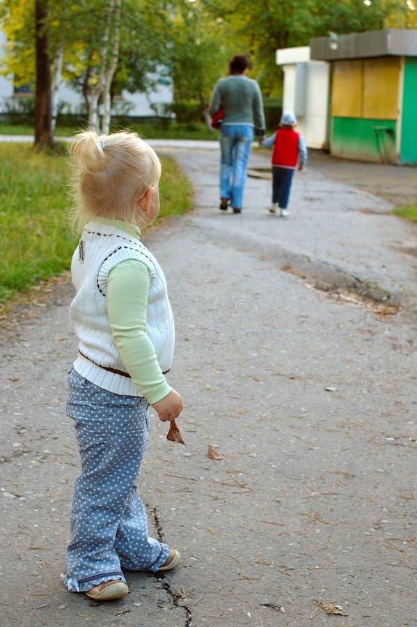 A menina sozinha vê na família (matriz e filho). foto de stock royalty free