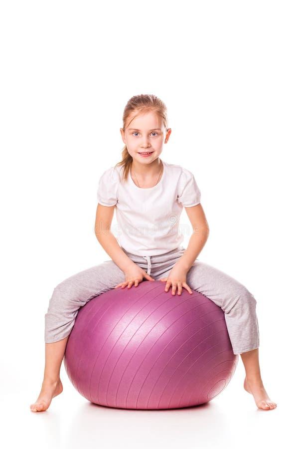 Menina Sportive em uma bola do ajuste imagens de stock