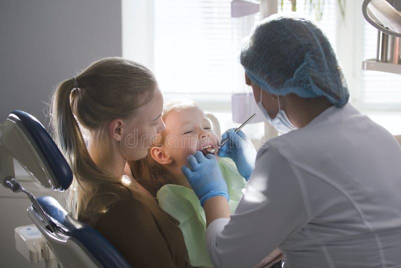 Menina, sua mamã e o dentista no escritório dental, o stomatologist examinando e consultando, filha jogando e imagem de stock