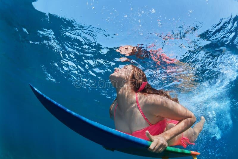 A menina surfando com placa mergulha sob a onda de oceano imagem de stock