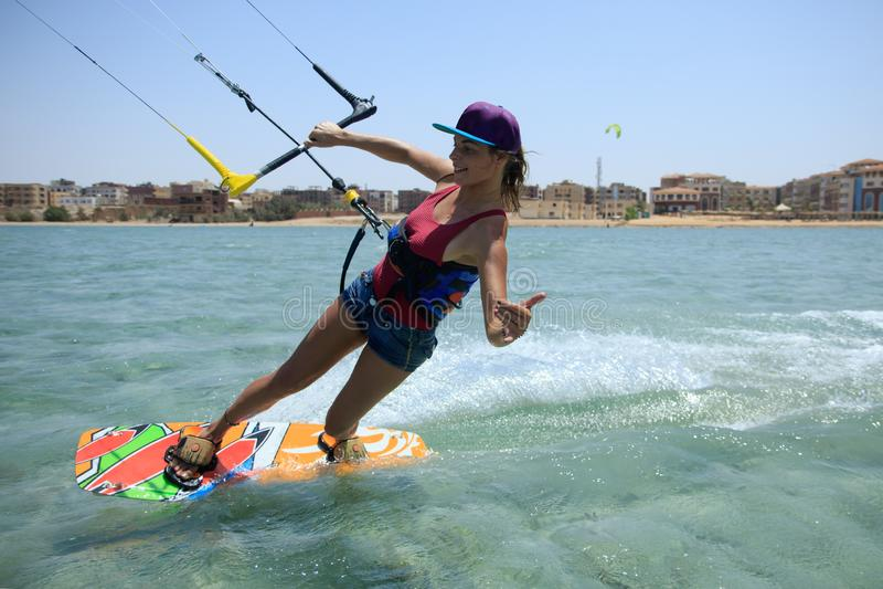 Menina surfando do papagaio no roupa de banho com o papagaio no céu a bordo em ondas de montada do mar azul com respingo da água  foto de stock royalty free