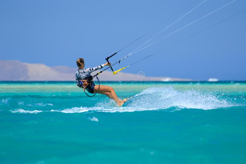 Menina surfando do papagaio no roupa de banho com o papagaio no céu a bordo em ondas de montada do mar azul com respingo da água  imagem de stock