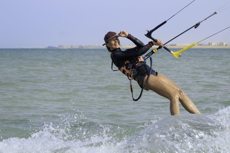 Menina surfando do papagaio no roupa de banho 'sexy' com o papagaio no c?u a bordo em ondas de montada do mar azul com respingo d imagem de stock