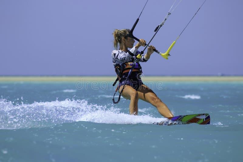 Menina surfando do papagaio no roupa de banho 'sexy' com o papagaio no c?u a bordo em ondas de montada do mar azul com respingo d imagem de stock royalty free