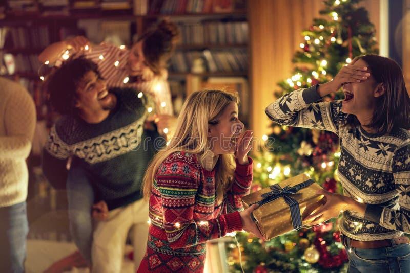 Menina surpreendente sua menina do amigo com um presente romântico no Natal Conceito do Natal da celebração e do ano novo imagens de stock royalty free