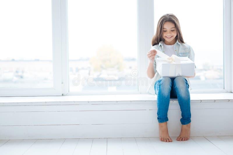 Menina surpreendida adorável que recebe seu presente fotos de stock royalty free