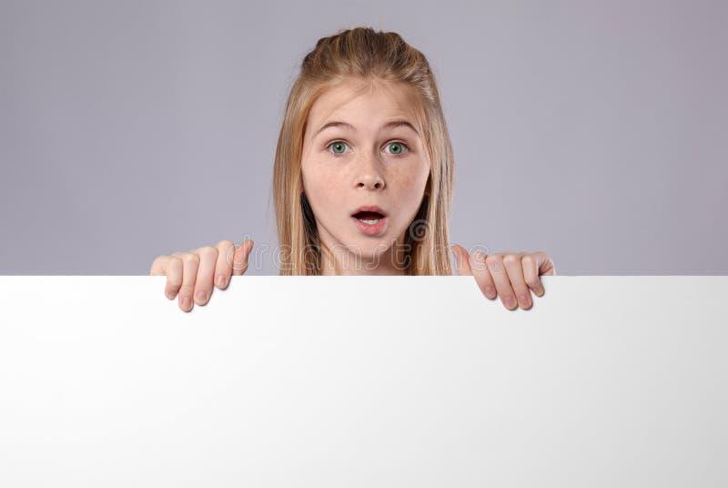 Menina surpreendida bonito com placa de propaganda vazia fotografia de stock