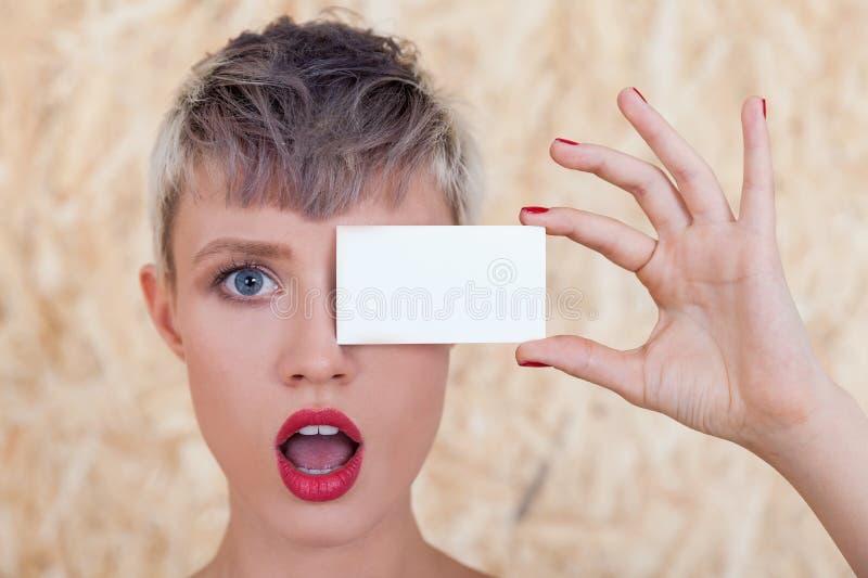 Menina surpreendida com o cartão perto do olho imagens de stock