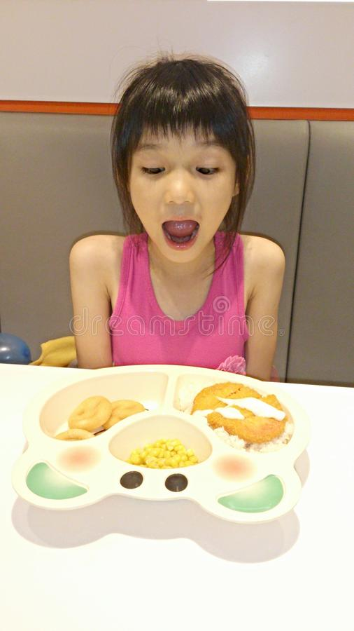 Menina surpreendida com seu alimento imagem de stock