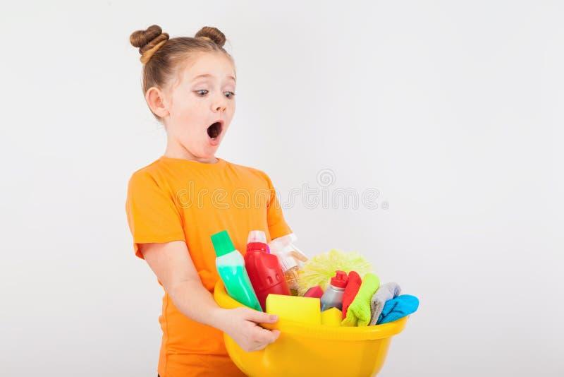 Menina surpreendida com uma bacia completa dos líquidos de limpeza fotos de stock royalty free