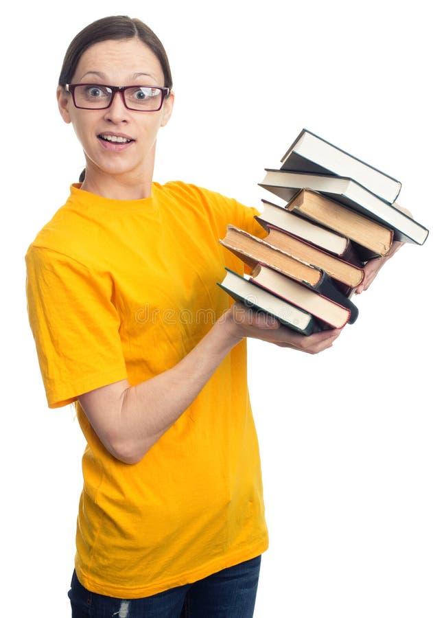 Menina surpreendida do estudante que guarda uma pilha de livros imagem de stock royalty free