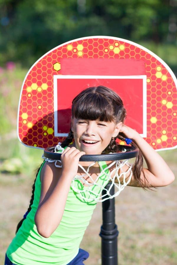 Menina surpreendida na aro de basquetebol fotos de stock