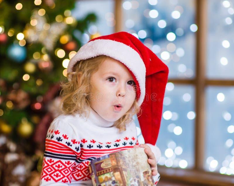 Menina surpreendida no chapéu vermelho do Natal com caixa de presente imagem de stock