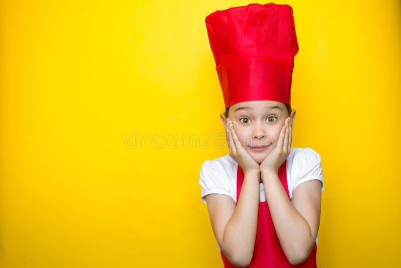 Menina surpreendida no terno de um cozinheiro chefe vermelho com mãos em mordentes no fundo amarelo com espaço da cópia imagens de stock royalty free