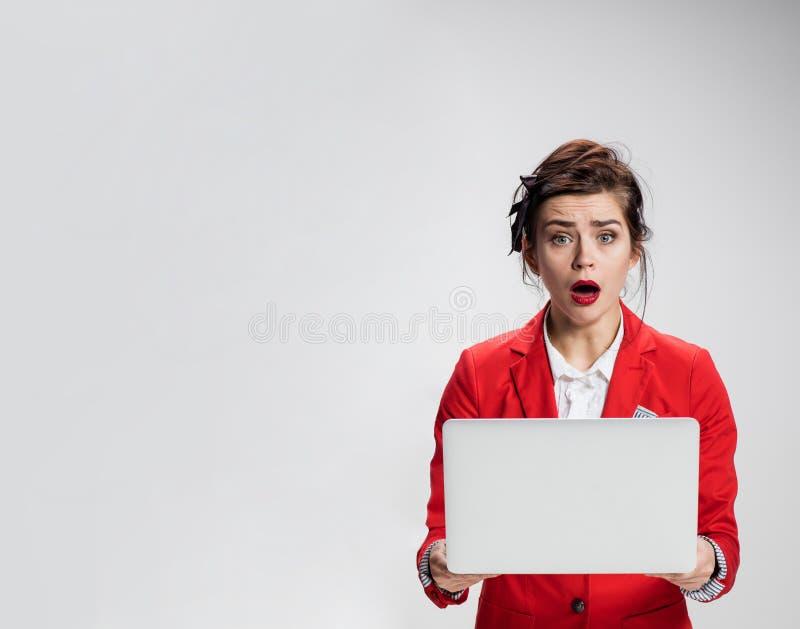 Menina surpreendida que guarda o portátil sobre o fundo cinzento imagem de stock