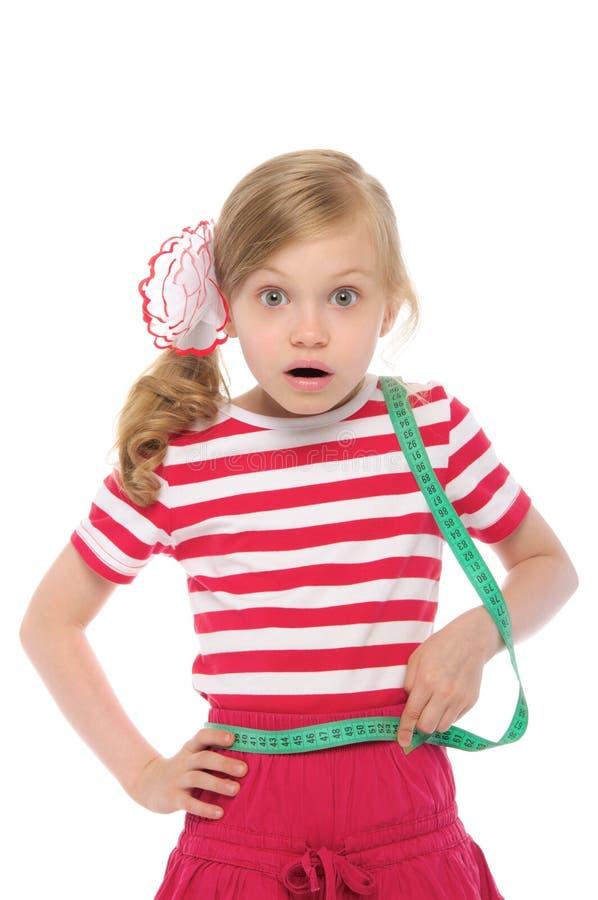 Menina surpreendida que mede sua cintura imagem de stock