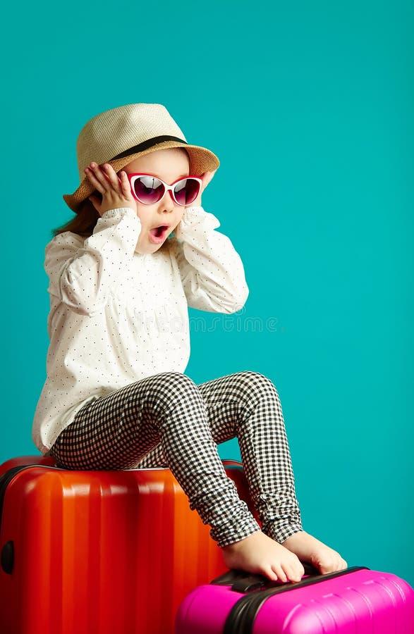 A menina surpreendida senta-se em malas de viagem, expressa a alegria sincera, pôs as mãos para enfrentar, demonstra a emoção pos imagem de stock
