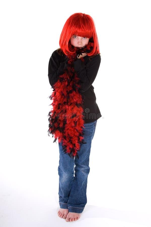 Menina tímida na peruca e na boa vermelhas. imagens de stock