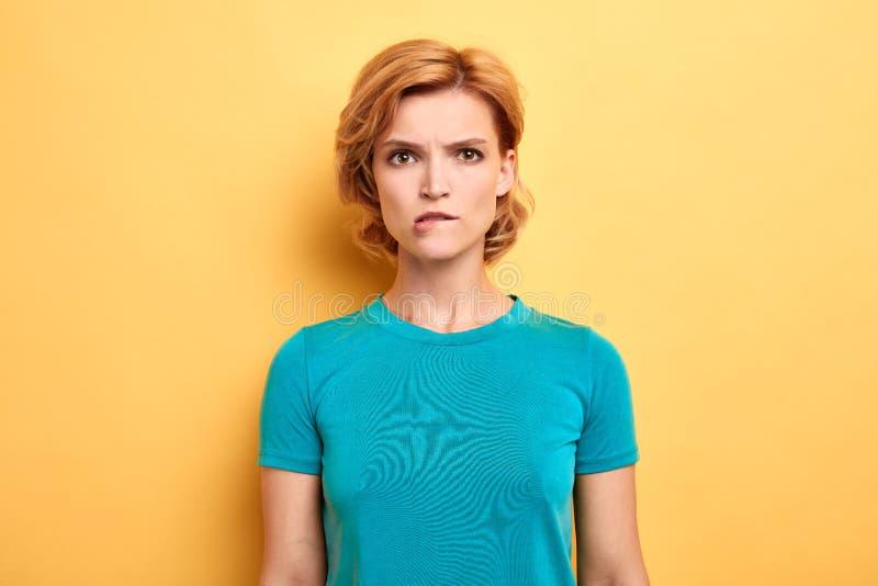 Menina tímida que veste o t-shirt azul que confunde a expressão imagem de stock