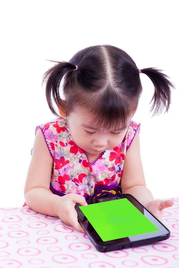 Menina (tailandesa) asiática pequena adorável que usa a tabuleta digital na mesa fotografia de stock royalty free