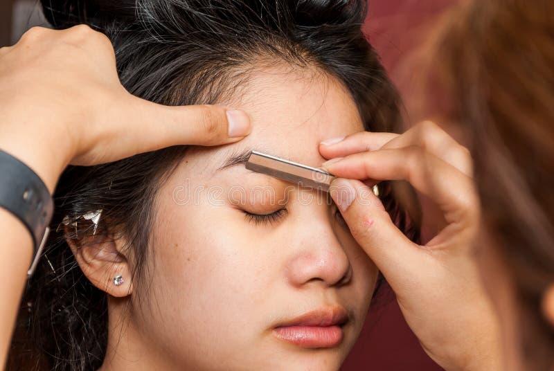 Menina tailandesa asiática que obtém a sobrancelha dada forma foto de stock royalty free