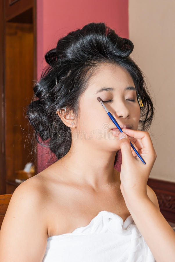 Menina tailandesa asiática que obtém a sombra para os olhos nas pálpebras imagem de stock royalty free