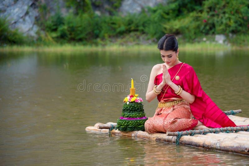 Menina tailandesa bonita que veste o vestido tradicional tailandês vermelho no festival de Loy Krathong fotos de stock