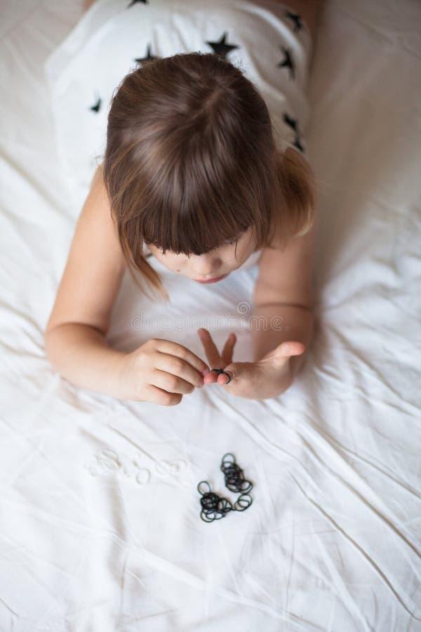 A menina tece a goma do bracelete da joia, faixa de trança da goma fotografia de stock