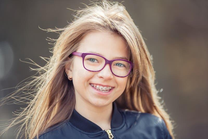 Menina teen Pre adolescente Menina com vidros Menina com cintas dos dentes Cintas e vidros vestindo dos dentes da menina loura ca imagens de stock royalty free