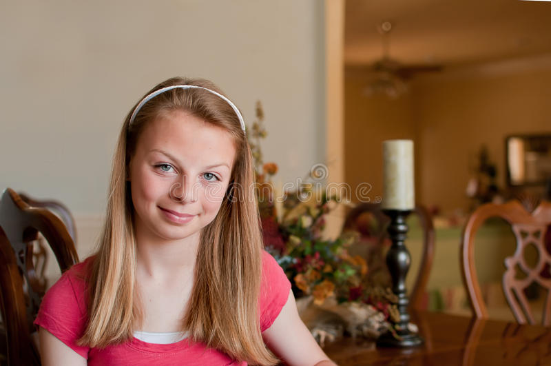 Menina Teenaged que senta-se na tabela de jantar de madeira fotografia de stock
