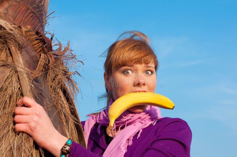 A menina tem o divertimento com uma banana foto de stock