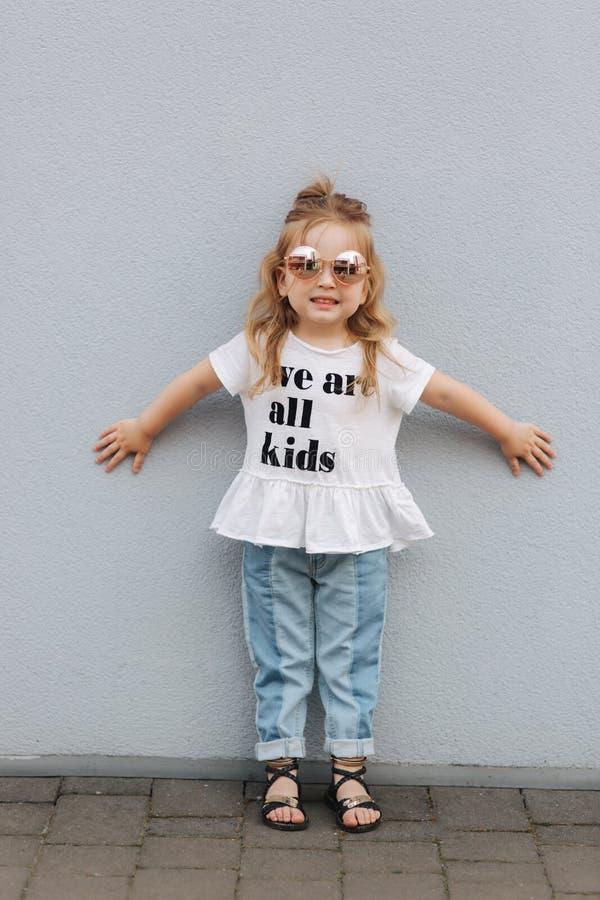A menina tenta sobre óculos de sol e levantamento ao fotógrafo fotos de stock royalty free