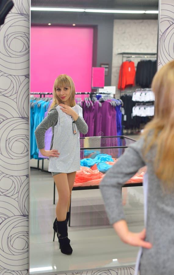 A menina tenta sobre um vestido novo na parte dianteira da loja de um espelho fotos de stock royalty free