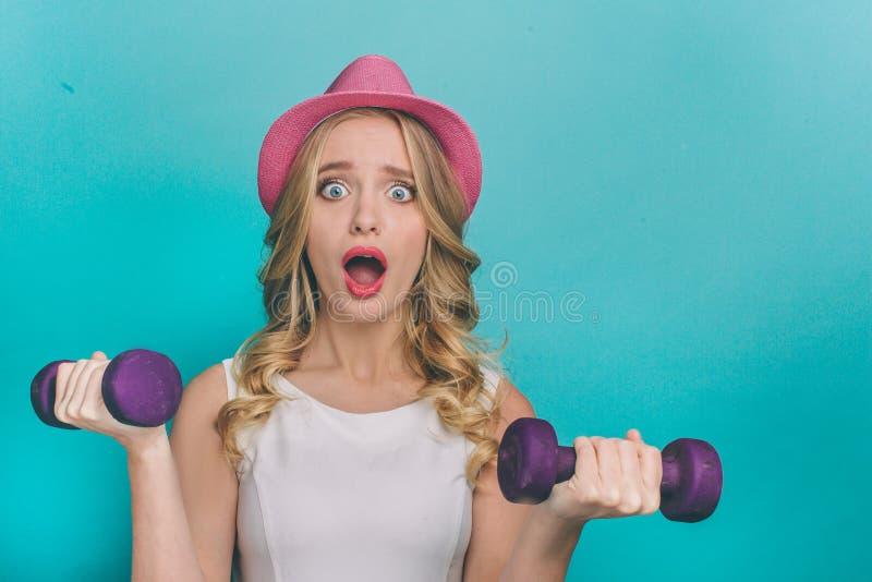 A menina terrificada está guardando dumbbels e está olhando diretamente a câmera Os dumbbels são pesados Ele ` s duramente para q imagens de stock