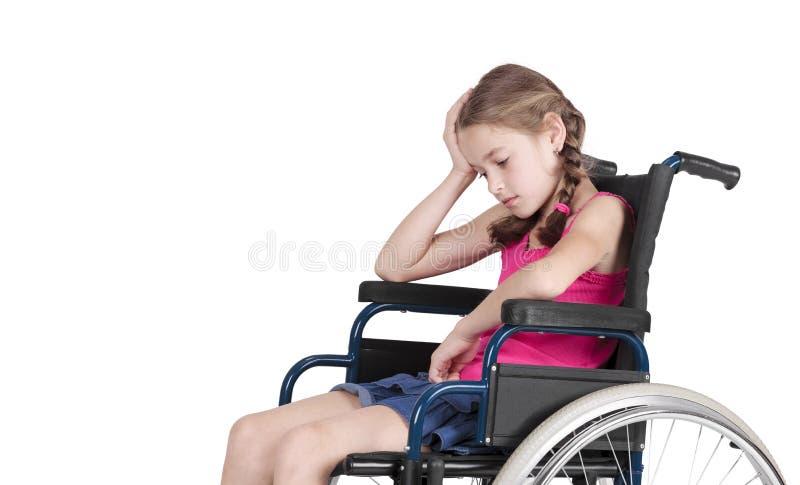 Menina tida desvantagens muito triste em uma cadeira de rodas fotografia de stock royalty free