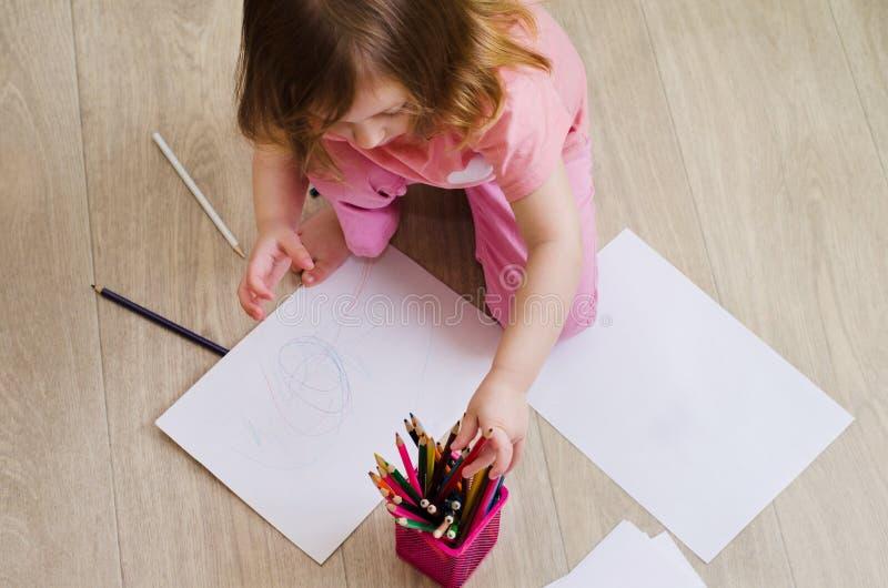 A menina tira com lápis coloridos imagem de stock