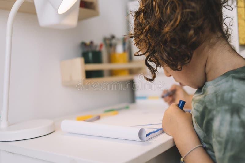 A menina tira com os marcadores da cor em sua mesa foto de stock