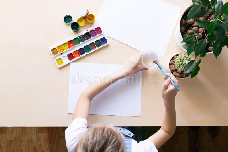 A menina tira com pinturas coloridas no Livro Branco na tabela Vista de acima Conceito da faculdade criadora e da educação fotografia de stock royalty free