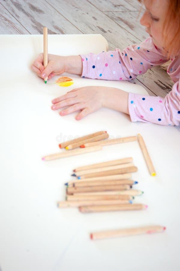 A menina tira em lápis coloridos foto de stock