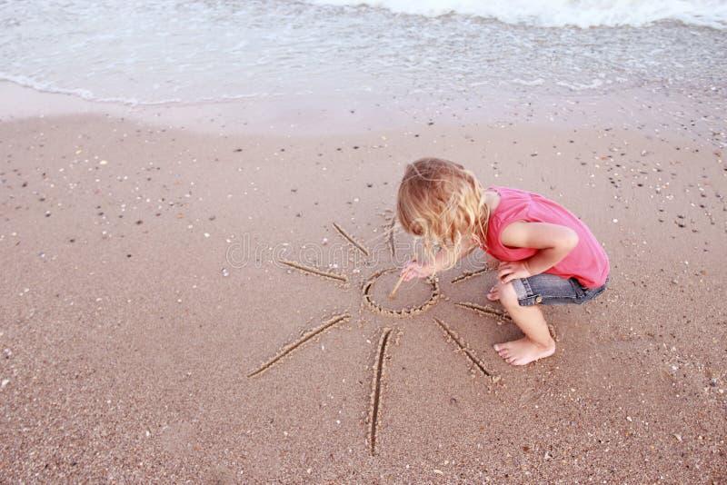 A menina tira um sol na areia na praia imagens de stock royalty free