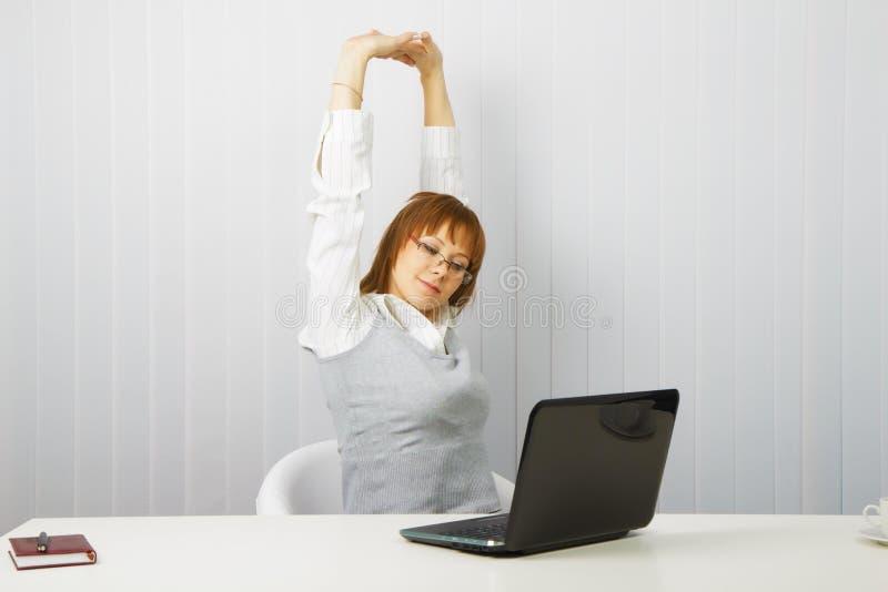 A menina Tired com um portátil estica fotografia de stock royalty free